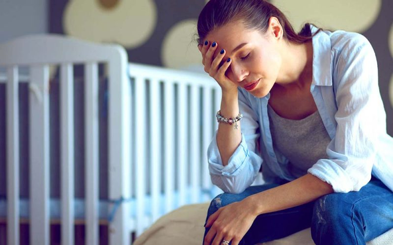 Postpartum Depression affecting a Mother, crib side; making her feel weak